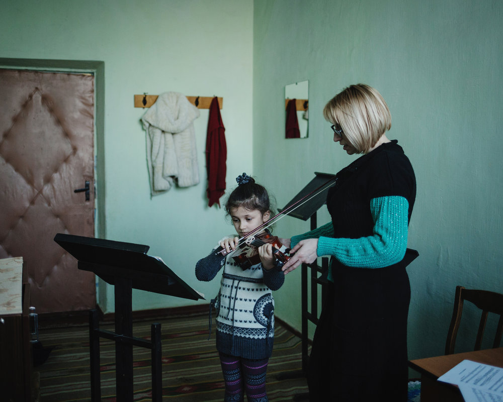 Evgenia Duloglu teaches violin to the young Arina in the House of Culture.