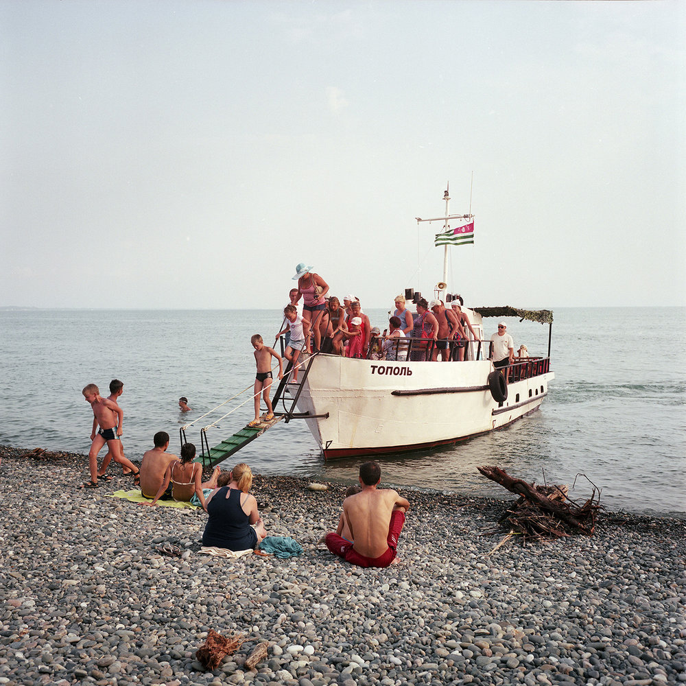 On the beach in Gagra. A boat comes take the tourists for an hour trip. The boat's captain was working on large fishing vessels in the past. Today, he renovated this boat and works for tourists.