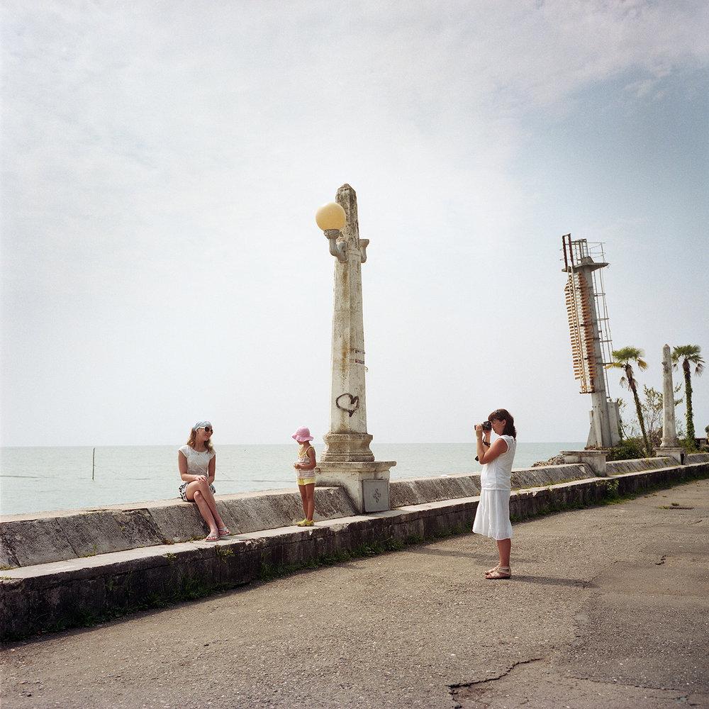 Tourists take photos in Sukhum(i) along the seaside.