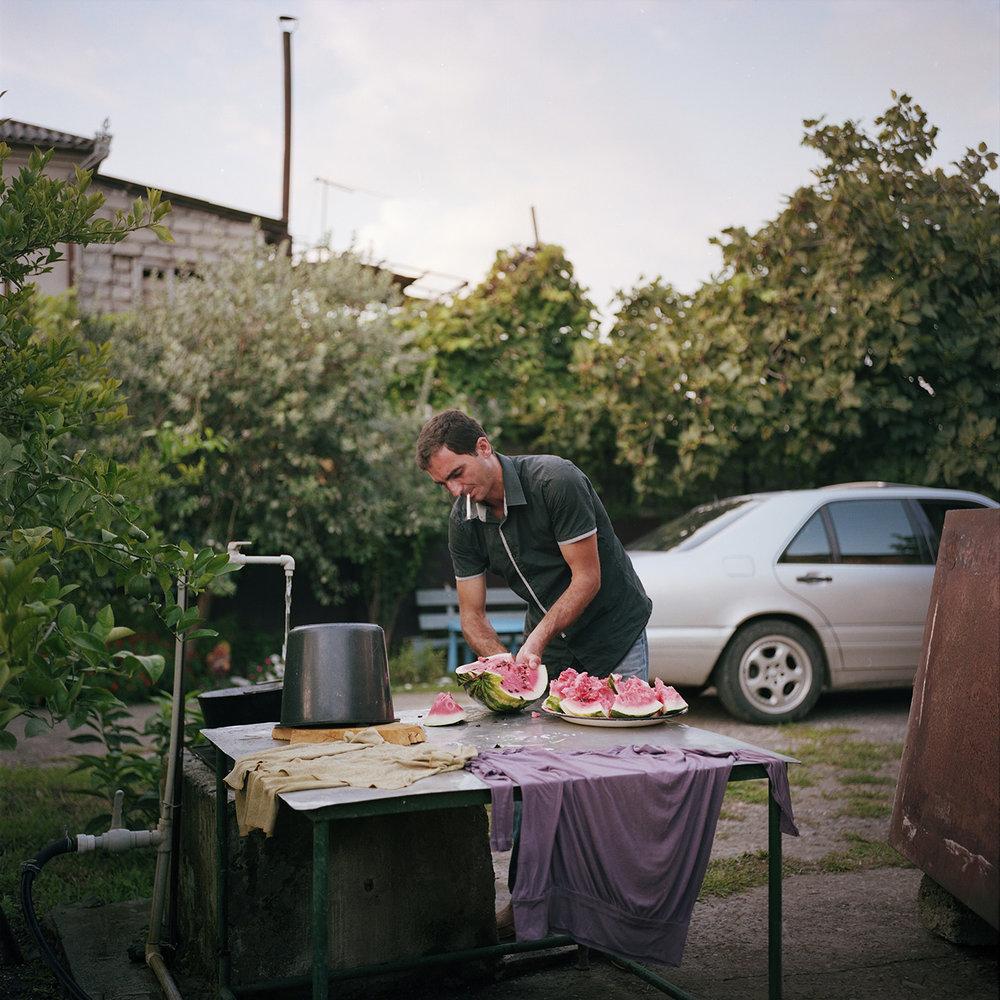 Samvel, an Armenian who lives in Sukhumi, cuts a watermelon in his garden where he grows mandarins.