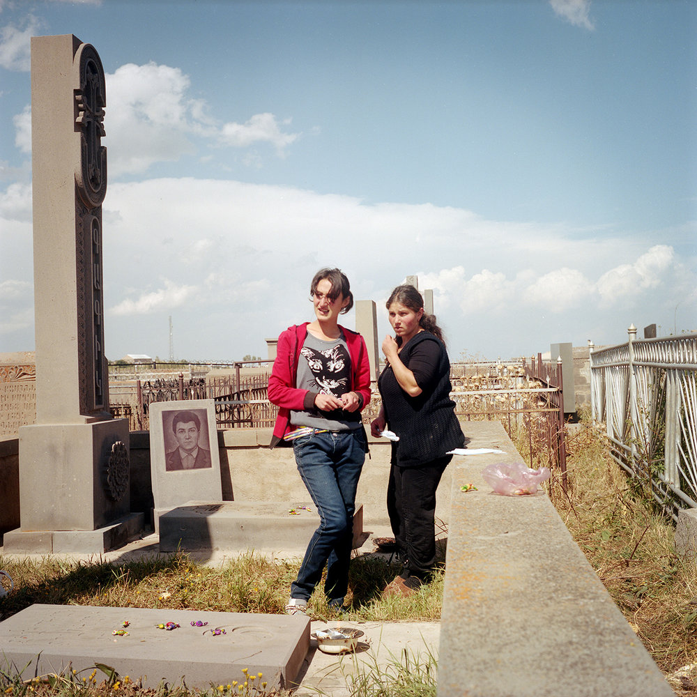 Today is the feast of the dead, the villagers go to the cemetery. They burn incense on the graves and will leave candy as offering. Ana (left) and Elvira (right) (cousins ​​by marriage) go there together. Their husbands are in Russia.