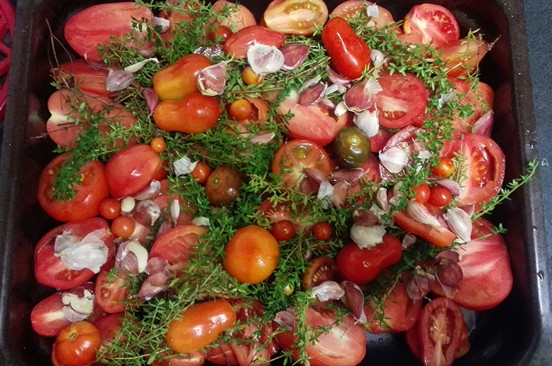 Roasting a tray of tomatoes with olive oil garlic and thyme