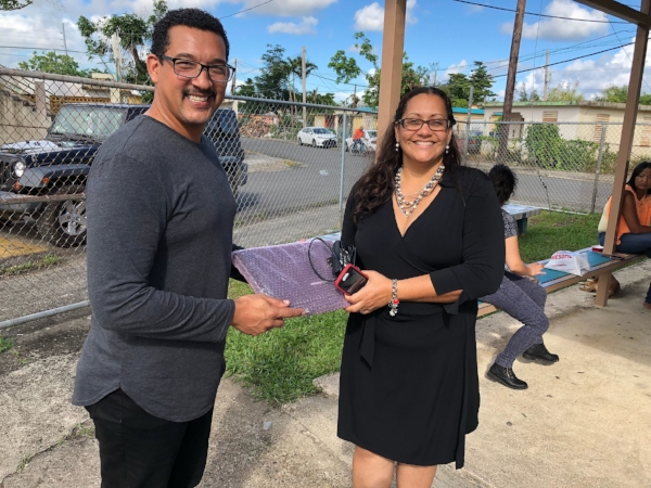 Jose Antonio Cochran, a legislator of education and sports from Patillas, and Frances Rivera, the Director of Escuela Guillermo Riefkhol in Patillas, accept our donation of a laptop to use as a tool in classrooms.