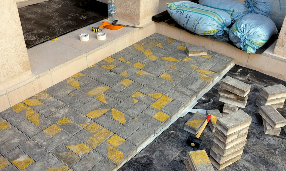Degenerative Disarrangement ,  2013  Pavement bricks with parallel yellow marks are removed from a site. At the exhibition site a hired mason installs the bricks within demanding time constraints workers regularly face, resulting in arbitrary patterns.