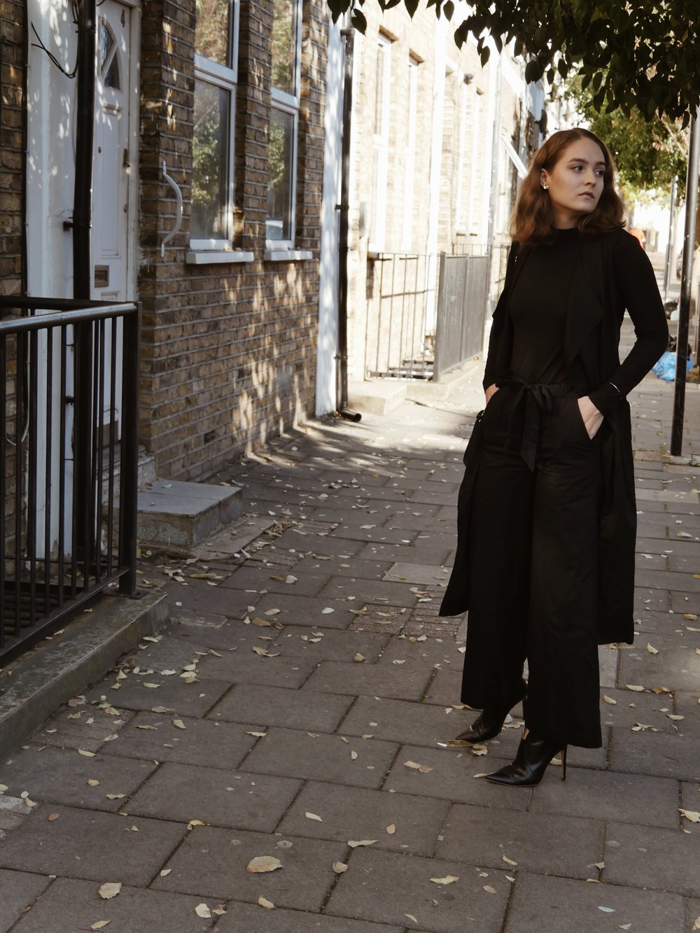 Livia wears a top and pants by  Miss Green , coat by  Studio Cossac , shoes by  Love Sofie , and bag by  LaBante London .