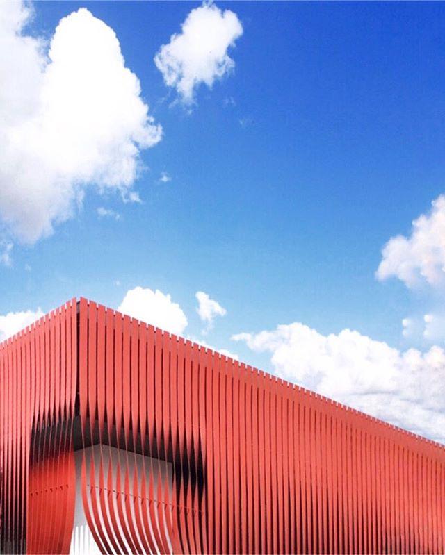 青い空を背景にランダムに湾曲している真っ赤なルーバーで覆われた外観 By Tokyo based Dutch architect Frank la Rivière  #franklarivière #ラリヴィエレフランク 🔵🔴