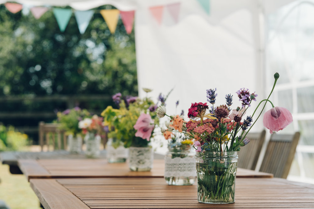 Wildflowers in lace jars with multicoloured bunting