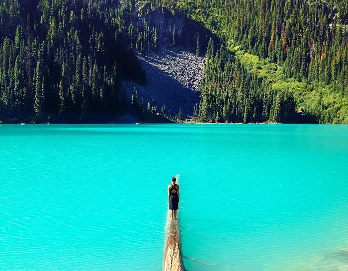 Woman+standing+on+log+in+water.jpg