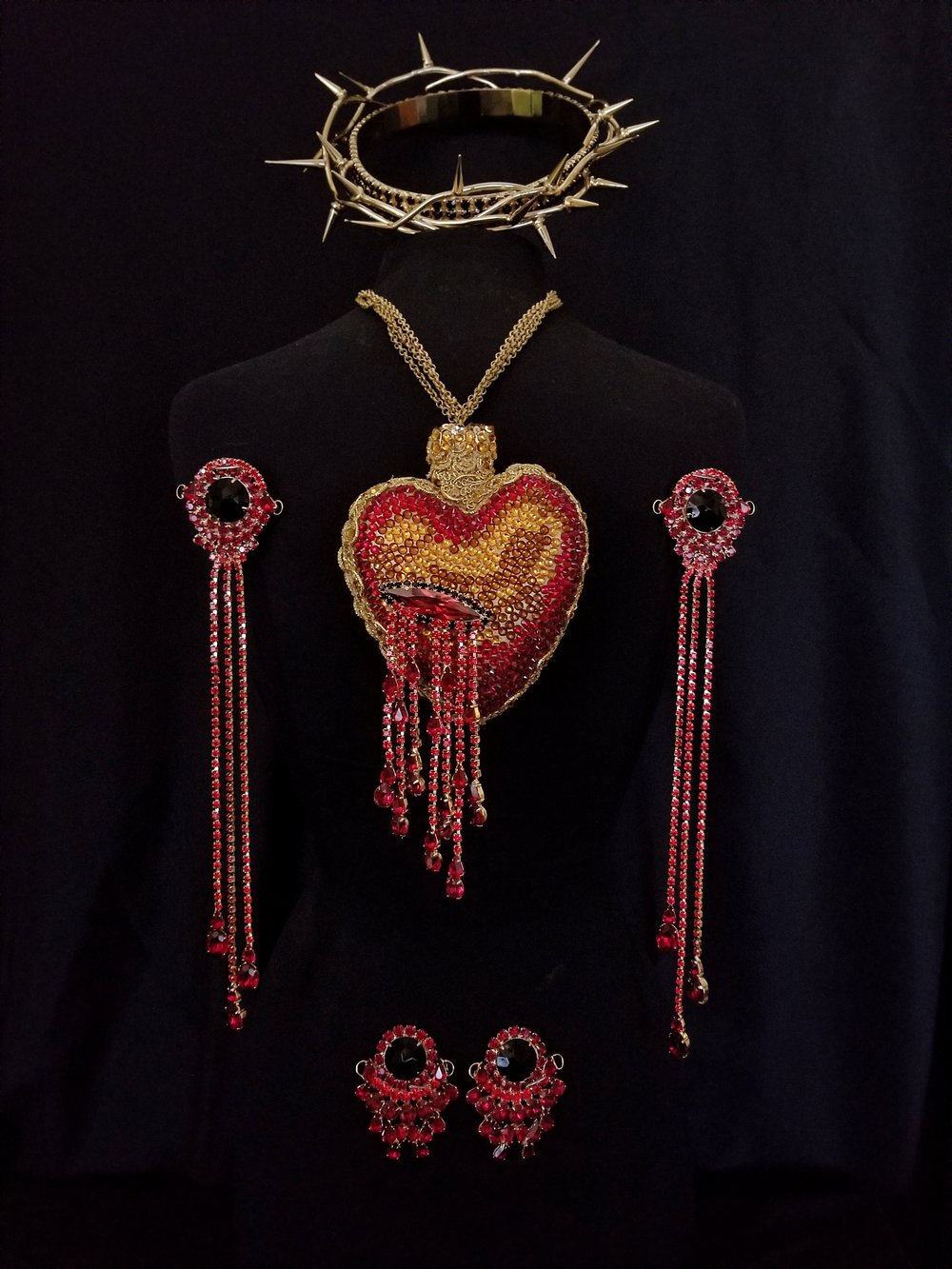 ☆ PASSION REGALIA ☆  Bespoke Sacred Heart pendant, palm stigmata with blood drop fringe, feet stigmata, and black diamond crown of thorns.    Light Siam, Siam, Garnet, and black diamond Swarovski and Preciosa crystal with gold trim and 24k gold plate.
