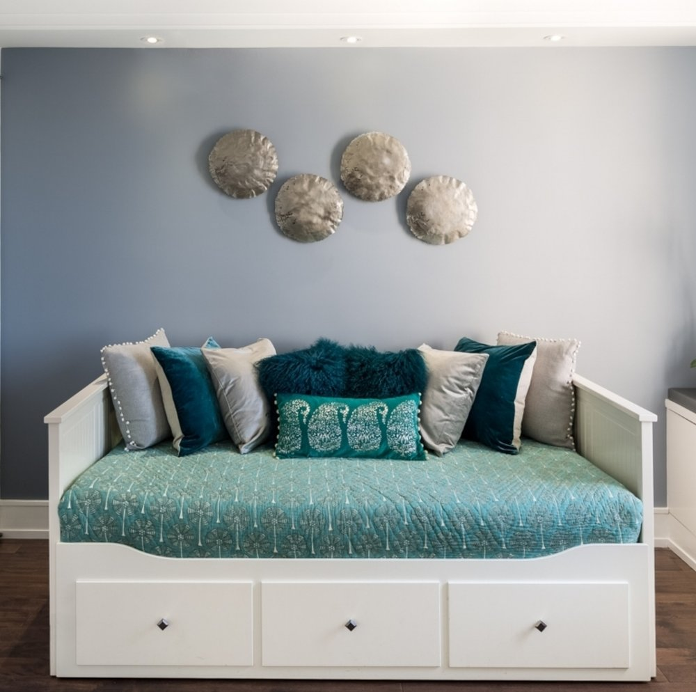 This daybed is layered with so many complimenting colors, textures, fabrics, prints and solids to create an overall inviting bed. There is the soft muslin quilted bedspread flanked by grey linen throw pillows with a pom pom detail, the emerald velvet cushion with a linen back, the silver velvet pillow - and they all meet with the faux fur emerald pillows. Also accented in the middle is a antique silver paisley printed turquoise velvet pillow with silver pom poms. Note how there are similarities between the colors, pom poms, linen, velvet over so many different design elements.  The moon crater metal art is hand finished with imperfections while painting the wall a darker color makes it a feature. The soft details are all about interior design and styling!