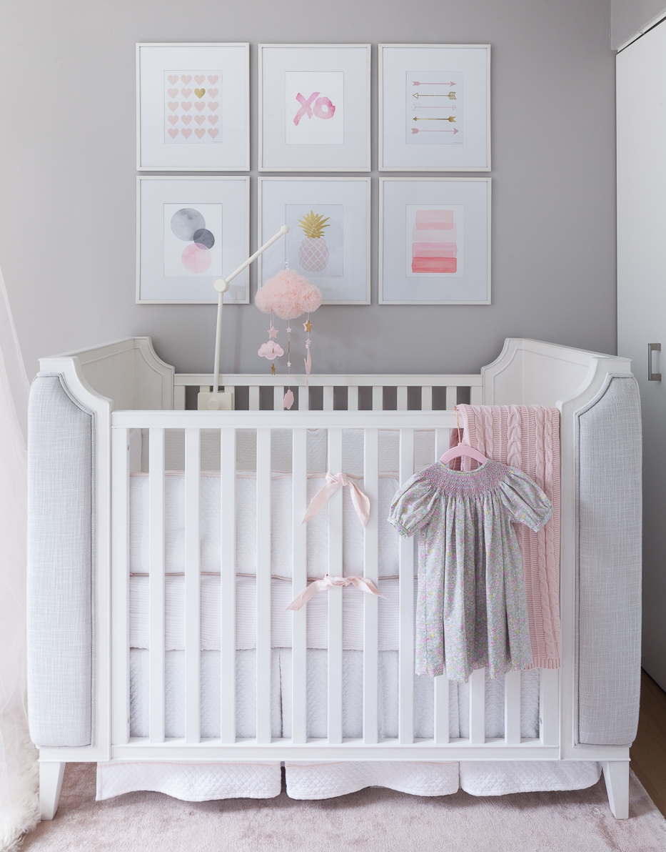 We love this crib with the upholstery on the sides, so luxurious. The details on the crib are adorable and enhanced with the bedding. Very neutral and tailored, diamond quilted bedskirt with a pink band at the bottom, striped fitted sheet and the little pink bow and welting at the bumper. The art above brings the whole room together with the colors and organic prints.  Needless to say, its a convertible crib in gray upholstery, if and when a baby boy should join the family.