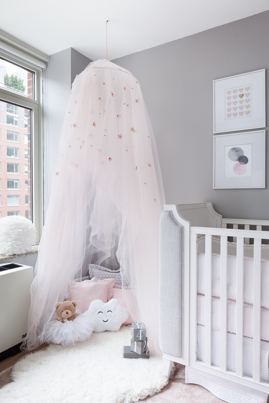 The Canopy in this nursery is really the design feature. The accessories play an important part in the story. The blush pink aacent pillows with the ruffle trim carry the color story forward and the ruffle trim keeps with the playfulness of the room. The fabric is linen and makes them appear casual. The grey cushions anchor the play area playing off the wall color and have a rouched stitching detail. Again the fabric is linen and works well with the linen on the crib. There are three cloud themed accents in the room on special request by the homeowner - the cloud pillow, the cloud in the mobile and the cloud shag rug anchoring the canopy.  The blocks bring some natural organic element to the picture.