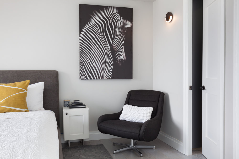Keeping with the black and dark moody greys throughout the house, we bring in the black and white zebra art. The art pulls together the room with the dark grey swivel chair making it the perfect spot for that morning cuppa joe. I love the slight peek into the custom dark wood walk in closet and the minimal black sconce we selected for lighting here. The crisp white quilt with the bright chartreuse is the perfect pop of color without being too obvious.