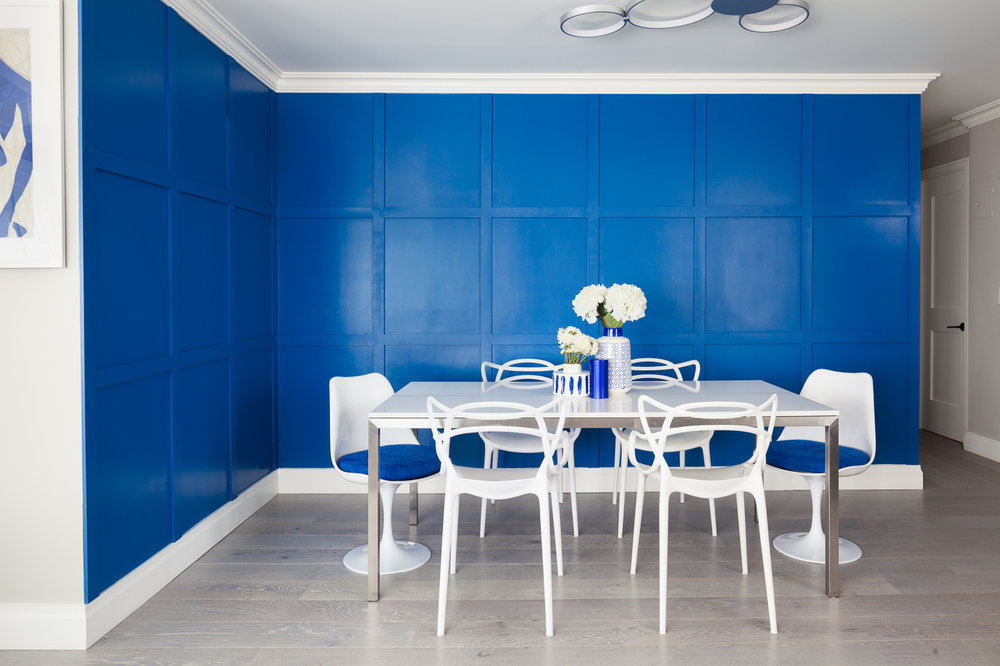 We anchored the dining room (not with a rug) but with a feature wall. We did custom square panelling creating a grid pattern and accented the room with a bright blue paint, a bold move.The Quartz top dining table is indestructible and beautiful at the same time. We love these dining chairs that add curves to the room amidst the geometry from the panelling. The assymetrical ceiling fixture provides a subtle movement to the design. The swivel chairs with the matching blue upholstery are details we live for.