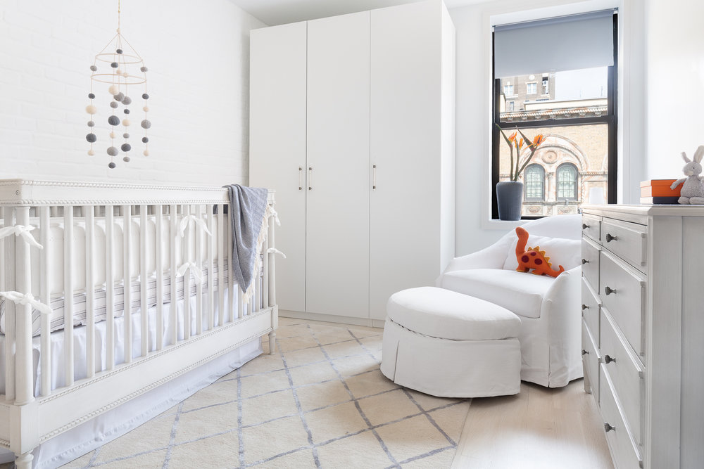 We love this crib with the border detail and its washed grey wood finish. We added some pale blue touches with the bedding and the rug. The round silohuette of the rocking chair brings so much softness. The felt ball mobile adds texture and playful character against the brick wall. Closets for critical storage and the black vase, ground the room.