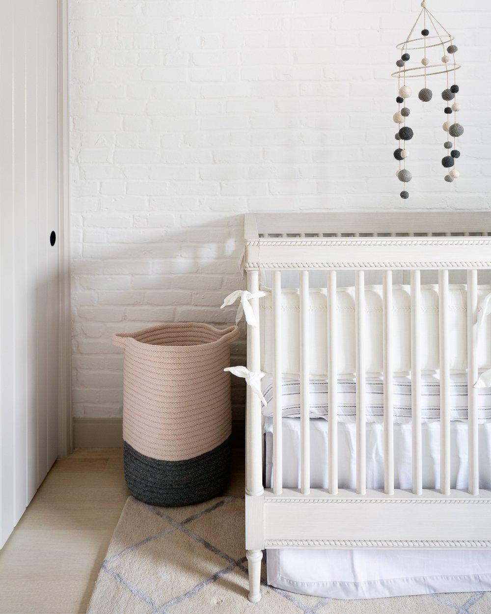We thought of everything… really. Laundry hamper is tucked away on the other side of the crib. Love the shadows against the brick wall and the closet door. The layers of bedding with ivory, whites and pale blue make it the coziest snooze zone in the neighborhood.