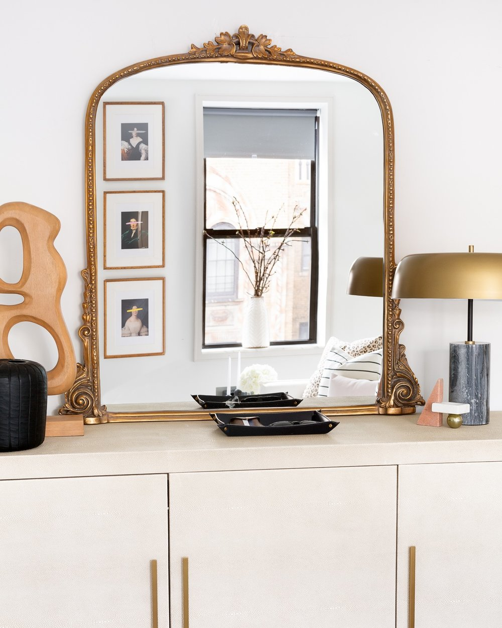 Another moment of luxe style. Sideboard in bone shagreen with brass hardware adorned with a beautiful antique mirror atop reflecting that beautiful art and those windows…. you know I love them by now!! The assymetric lamp with a marble base and brass shade adds a modern charisma to it.