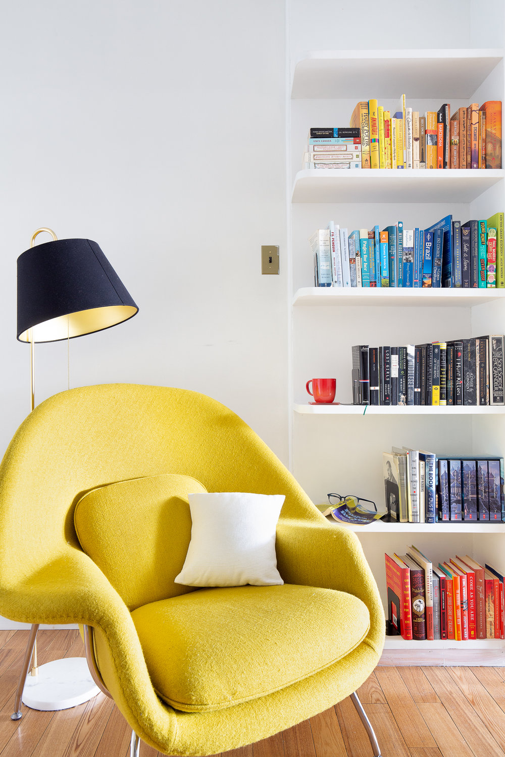 The design classic WOMB chair in a beautiful Chartreuse Felt with chrome legs is the main feature in the room againt backdrop of this amazing bookshelf styled by color.
