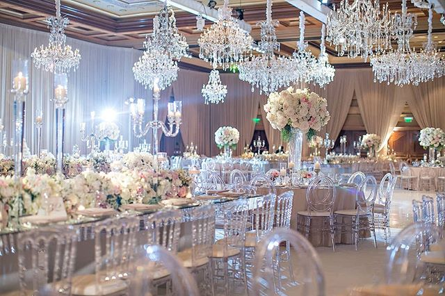 Dozens of crystal chandeliers hung overhead in the reception ballroom (Venue: @fairmontgranddelmar | Planning/Design: @internationaleventco @margot_iec | Florals: @marksgarden @michael_MarksGarden | Lighting: @thelightersidela | DJ Band: @liventgroup | Photographer: @jessicaclaire | Videographer: @davidmedillproductions | Rentals: @palacepartyrental | Cake: @jandlcakes)
