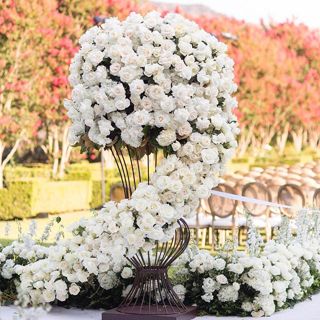 Oversized floral arrangements of roses, hydrangeas and magnolia leaves for the start of @jennifer_chaplin_tolkin bridal aisle (Ceremony Venue: Private Residence | Reception Venue: @bevhillshotel | Planning & Design: @internationaleventco @margot_iec @leeschrager | Floral Design: @marksgarden | Photo: @walker.studios | Video: @hoo_films | Décor/Furniture: @revelryeventdesign @matiasdoorn | Lighting: @images_lighting | Rentals: @tacer_losangeles | Caterer: @wpcatering | Music: @westcoastmusicbevhills | Specialty Performer: @jlo | Sound: @design.sound | Linens: @latavolalinen | Invitation Design & Printed Material: @cecinewyork)