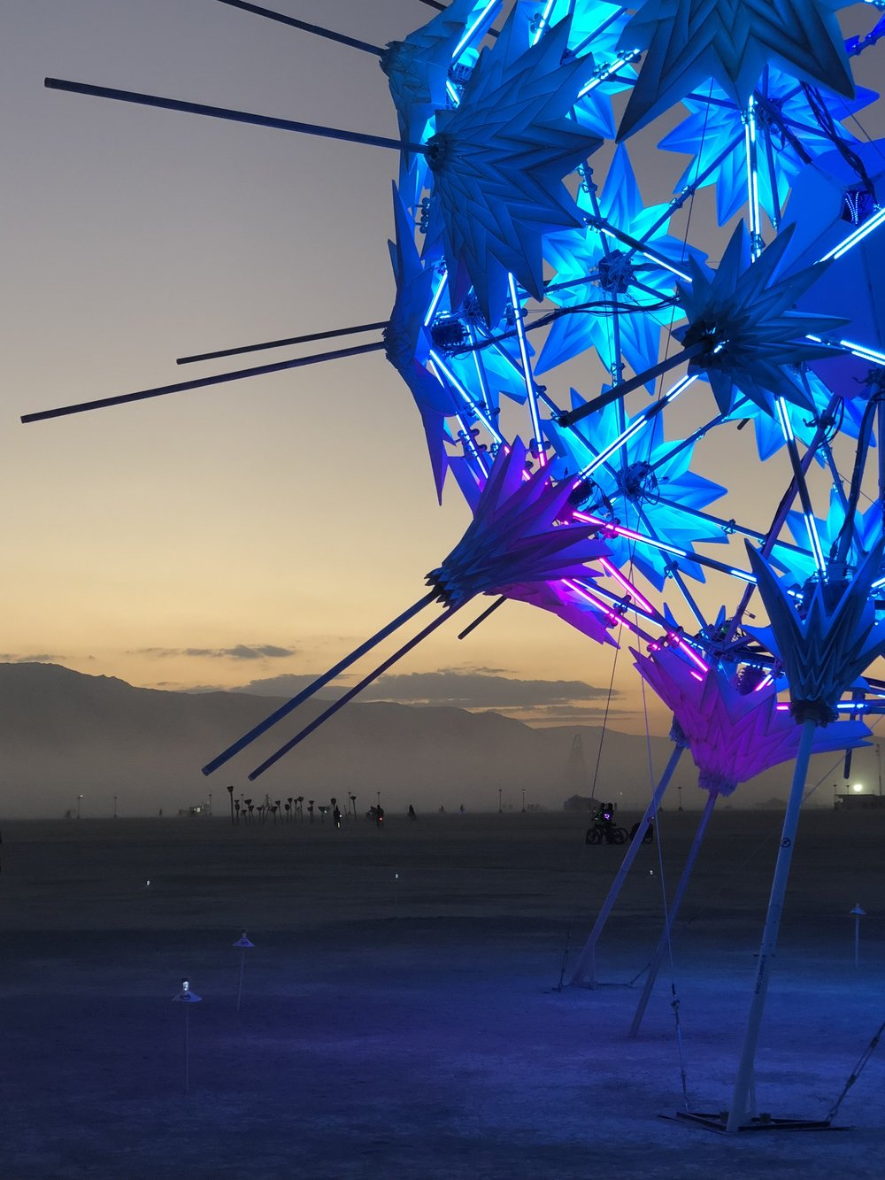 RadiaLumia   (2018) A geodesic sphere, five-stories tall, and covered with a breathing skin of origami shells and radiant spikes. The shells open and close in response to visitors' interactions inside. RadiaLumia premiered at Burning Man 2018.   Photograph by Steve Moore   [ See more ]