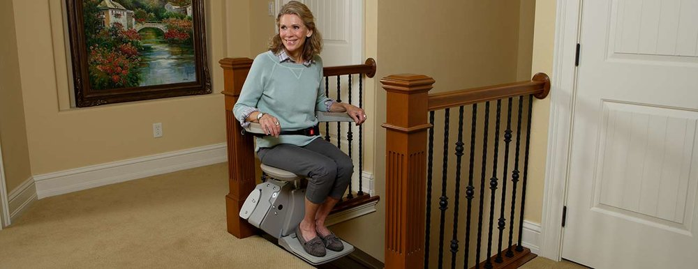 Bruno-Elan-stairlift-lady-riding-top-of-stairs.jpg