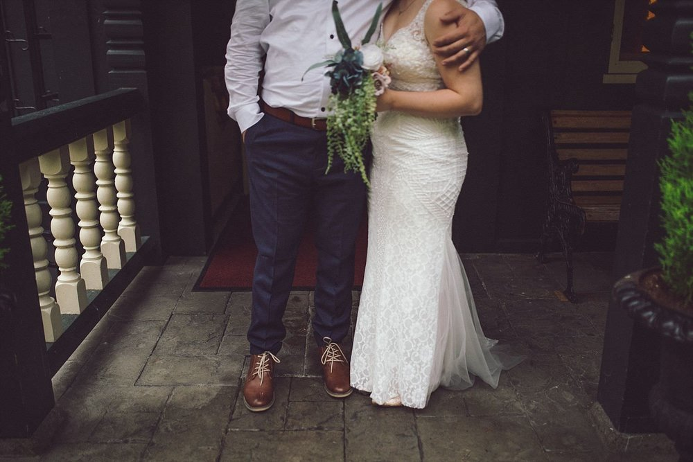 Groom in blue H&M pants and shoes, bride in beautiful lace white dress standing on front porch of Minnekhada Lodge