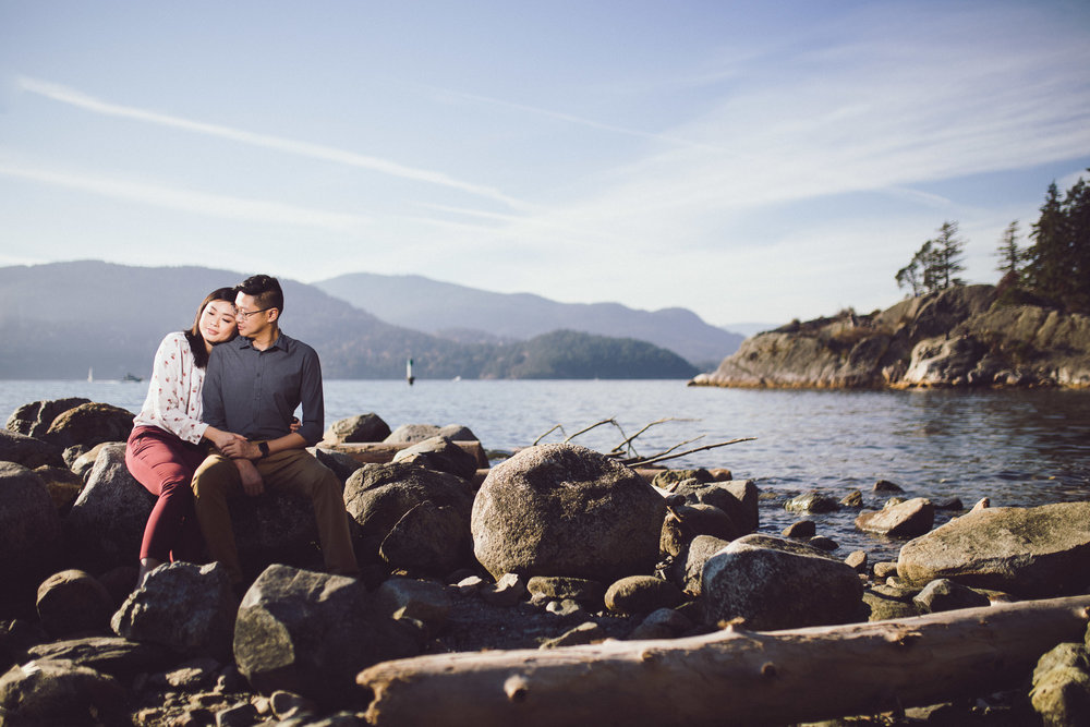 Engaged couple sitting on the rocks on the beach at Whytecliff Park