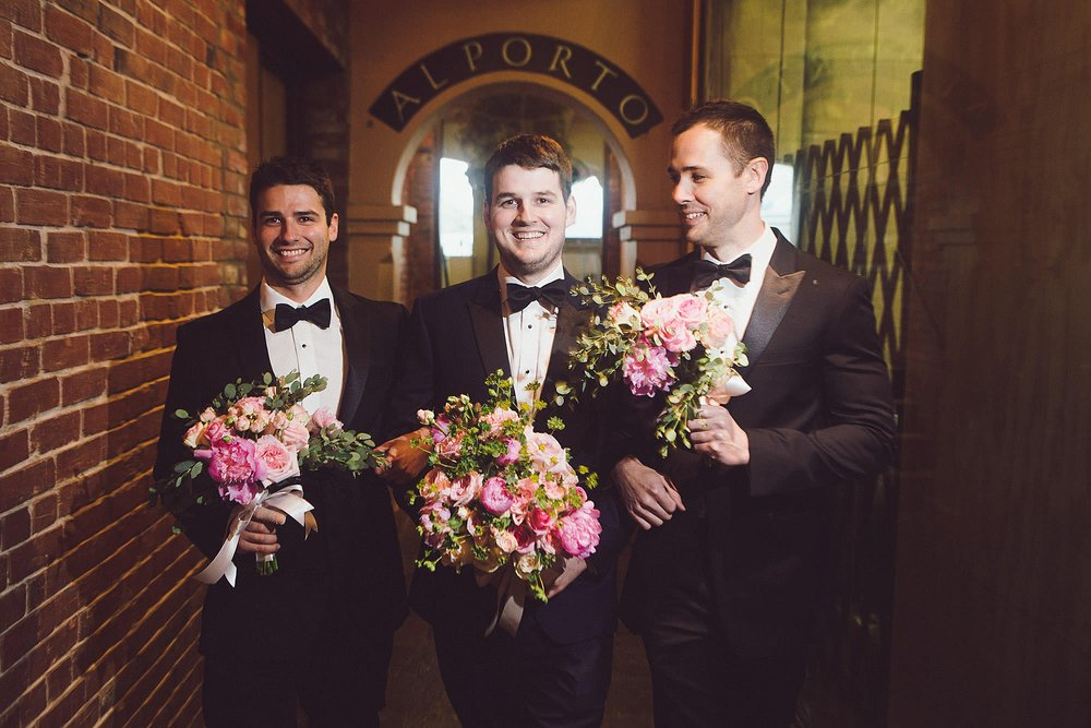 Groom and groomsmen holding flowers