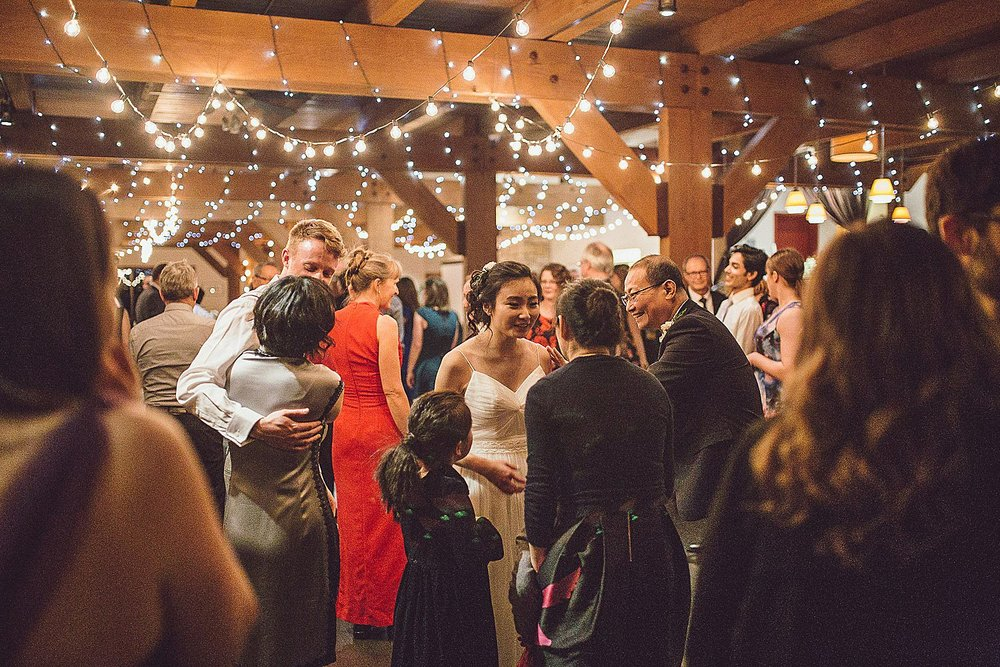Bride and Groom dance with family at their reception