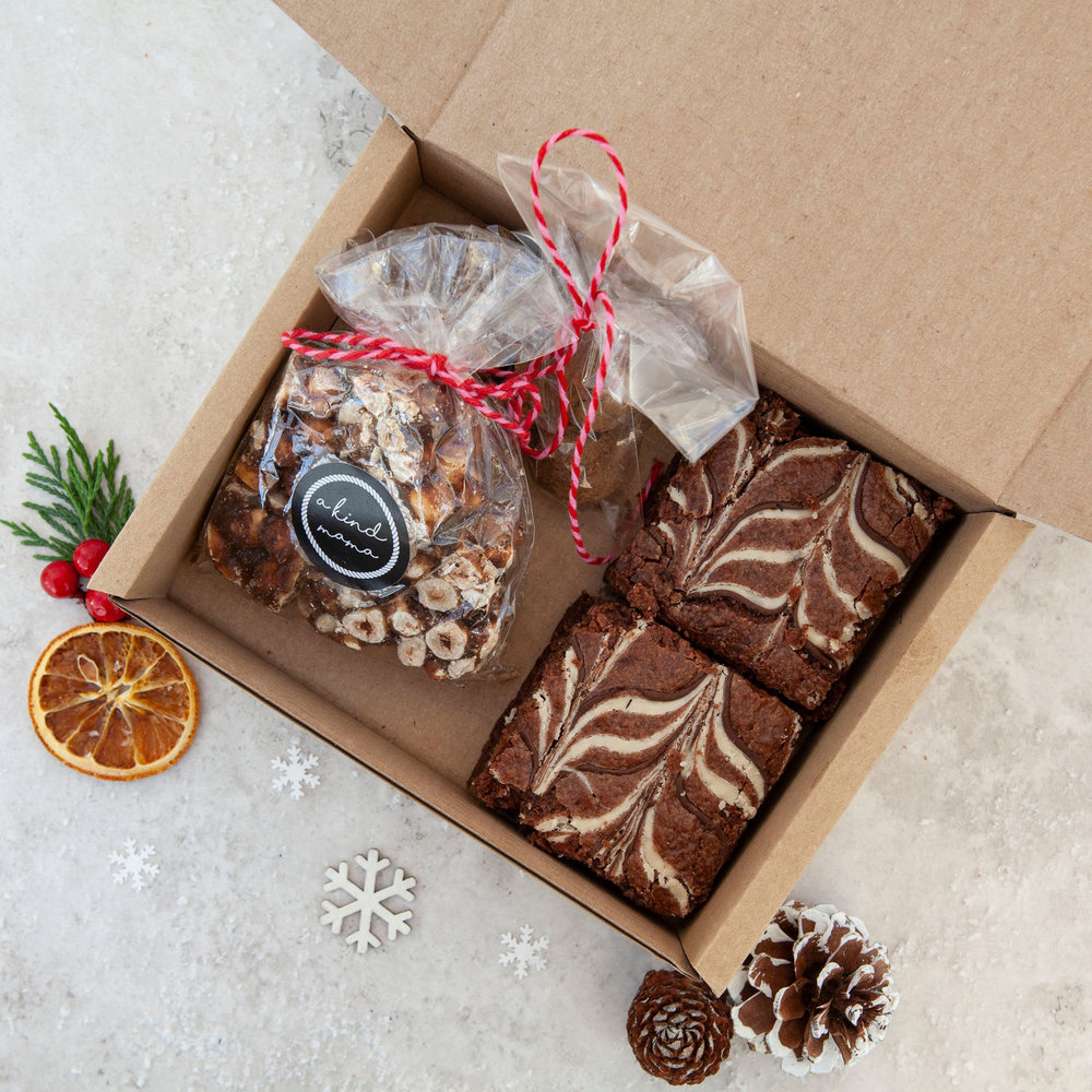 MIXED CHRISTMAS TREAT BOX - A Kind Mama Vegan Bakery was started as owner Eve couldn't believe it was so hard to find yummy vegan cakes. Eve just didn't think it was fair that living a cruelty free life meant people were missing out, so she started A Kind Mama Vegan Bakery. All products are 100% egg & dairy free, suitable for vegans and those with allergies.The best gift for vegans & non vegans alike this Christmas is this Christmas take on their classic Mixed Treat Box, which includes, two vegan Baileys brownies, with dark & vegan white chocolate swirled on top, a bag of A Kind Mama peanut brittle and four Truffle Pig vegan chocolate truffles. These also come gift wrapped free of charge.