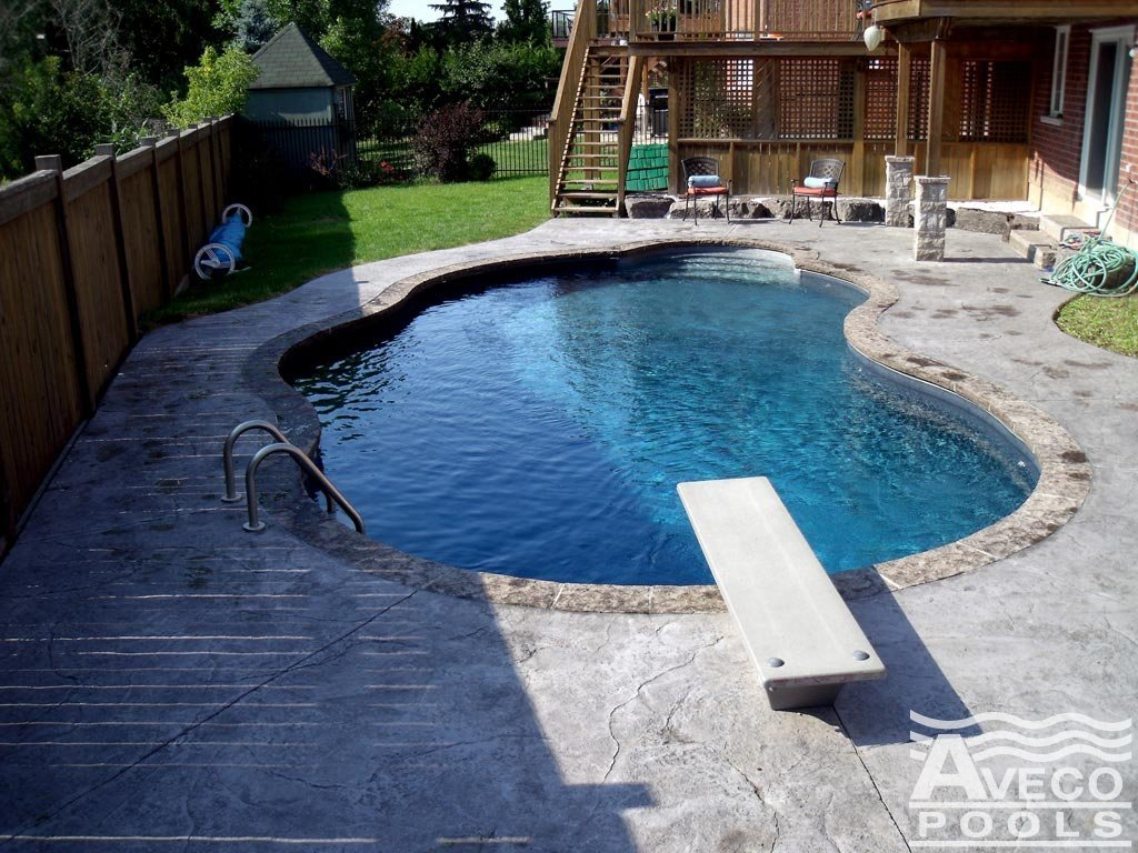 Inground Pool With A Stone Deck In The Backyard