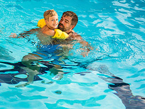 Father Teaching Son to Swim in Pool