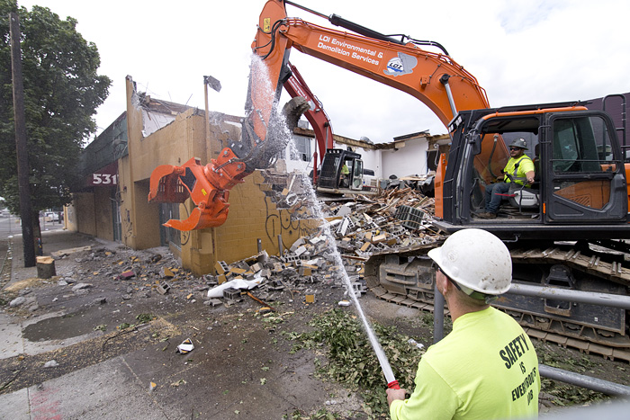 Jake Wagner, bottom right, of LOI Environmental & Demolition Services, sprays to contain dust Tuesday morning during the demolition of the former Portland Music Co. building on Southeast Martin Luther King, Jr. Boulevard.