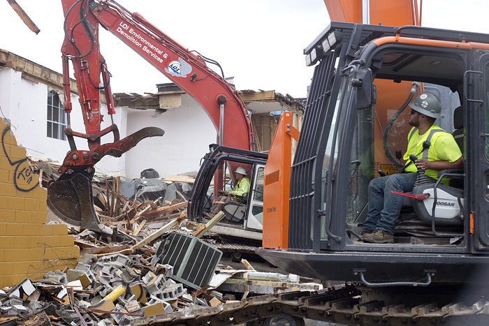 LOI employees Kyle Berens, foreground, and Jeff Wagner demolish the structure.