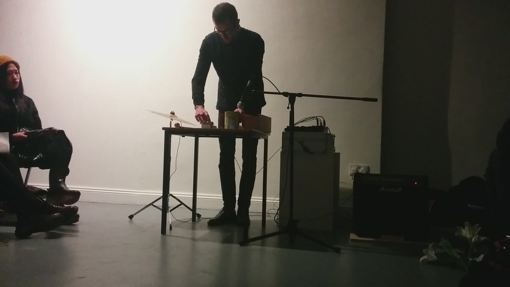 ^Performing Approaching The Object at Constantly Evolving But Never Ending, Angus-Hughes Gallery, London 2015 using cocoa tin, metal ruler amplified table top, glass jar, cymbal and various found and collected objects.