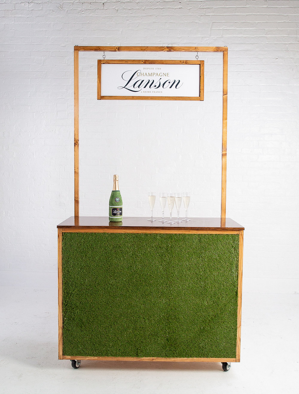 Quirky Group Grass Bar for hire with champagne