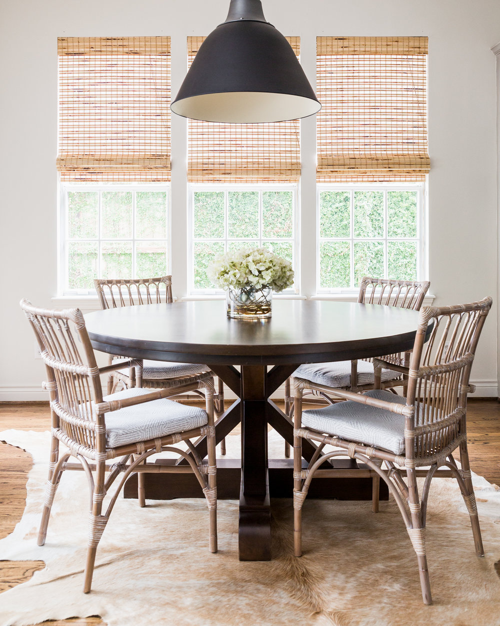 Farmhouse Dining Table with cowhide rug and rattan breakfast chairs