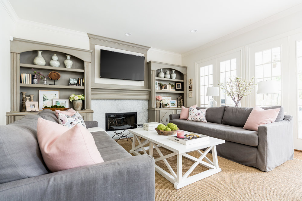 Family Room with Two gray sofas large coffee table and marble fireplace