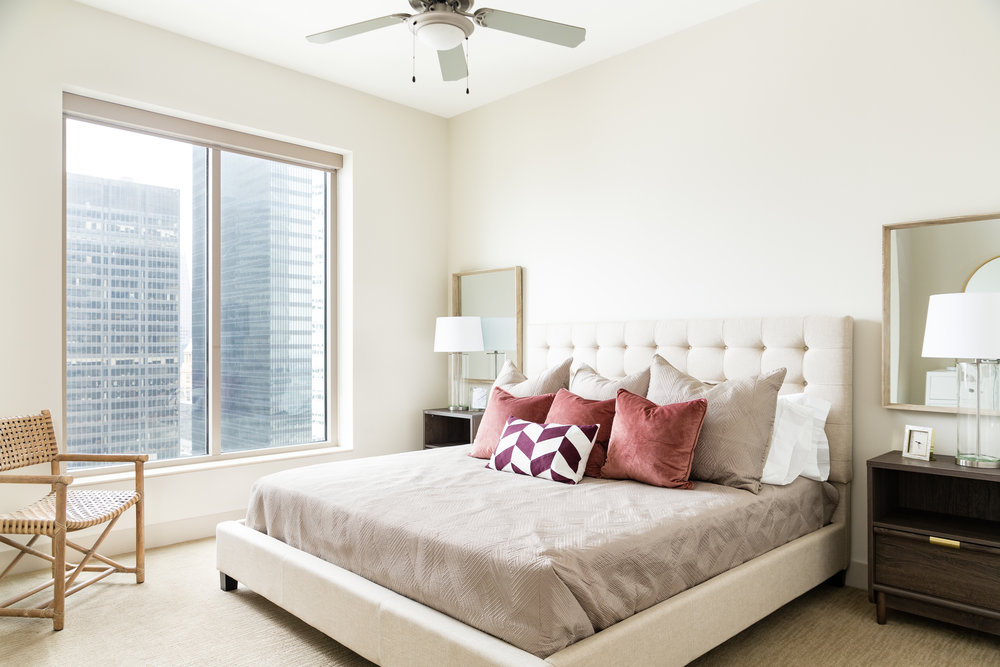 High rise bedroom with tufted bed and mirrors above nightstands