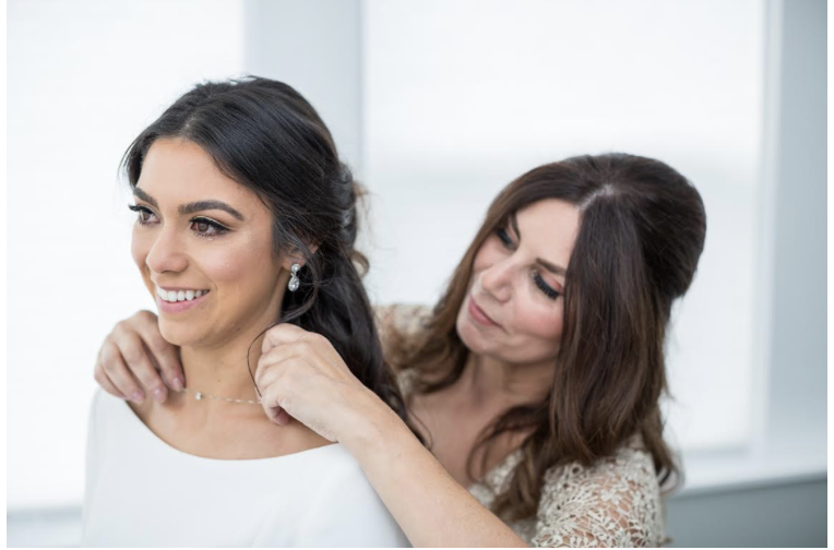 Sidney on her wedding day with her mom placing a necklace on her that encompasses the same diamond that was on the ring her father gave her mother.