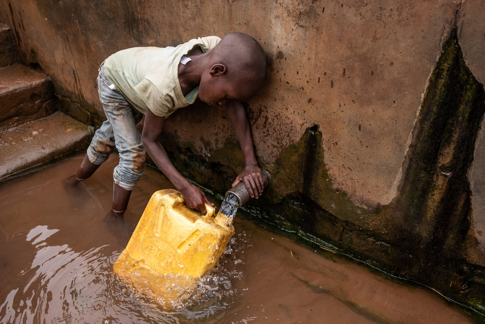 A young child collecting water in Kamuli, Uganda