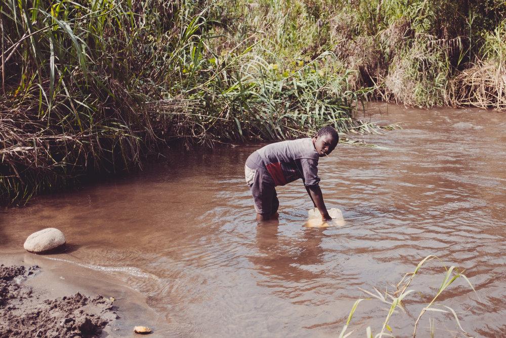 A young boy collecting water in Kiburara, Uganda