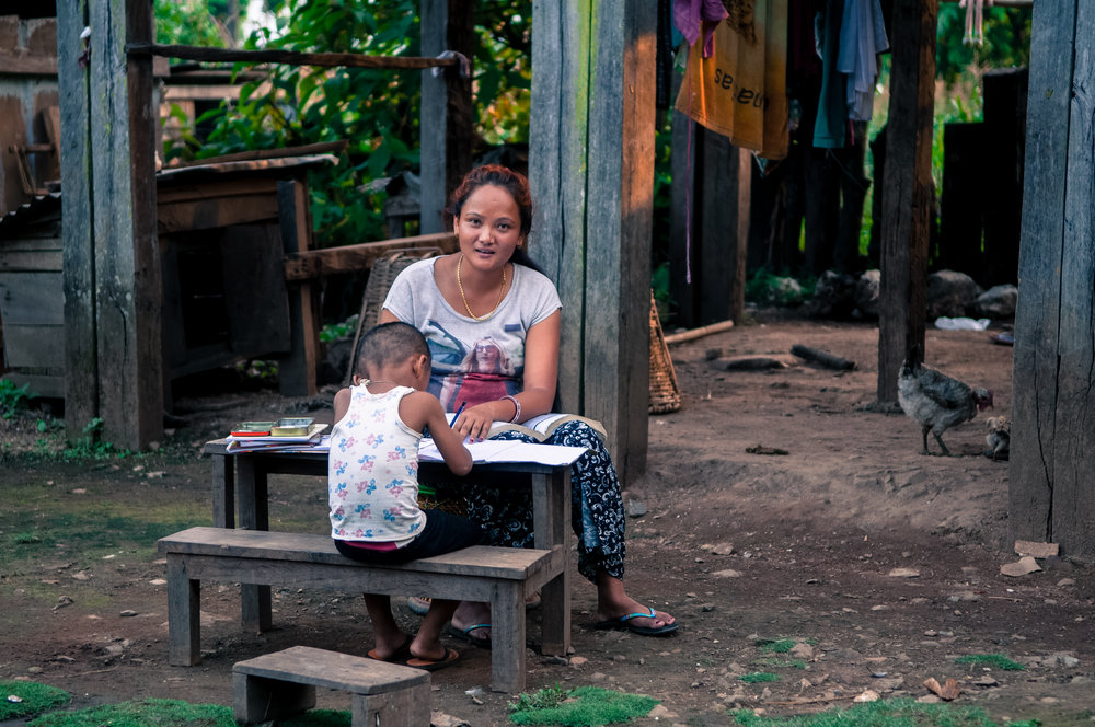 Young mother doing homework with child in Chepang, Nepal
