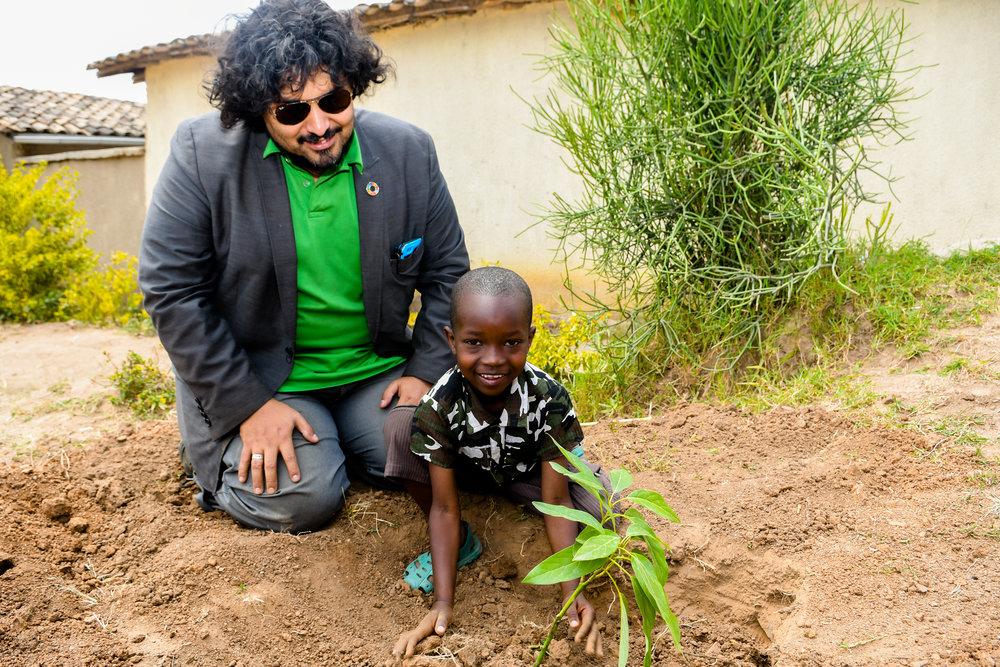 Clayton Louis Ferrara planting trees with Child in Rwanda