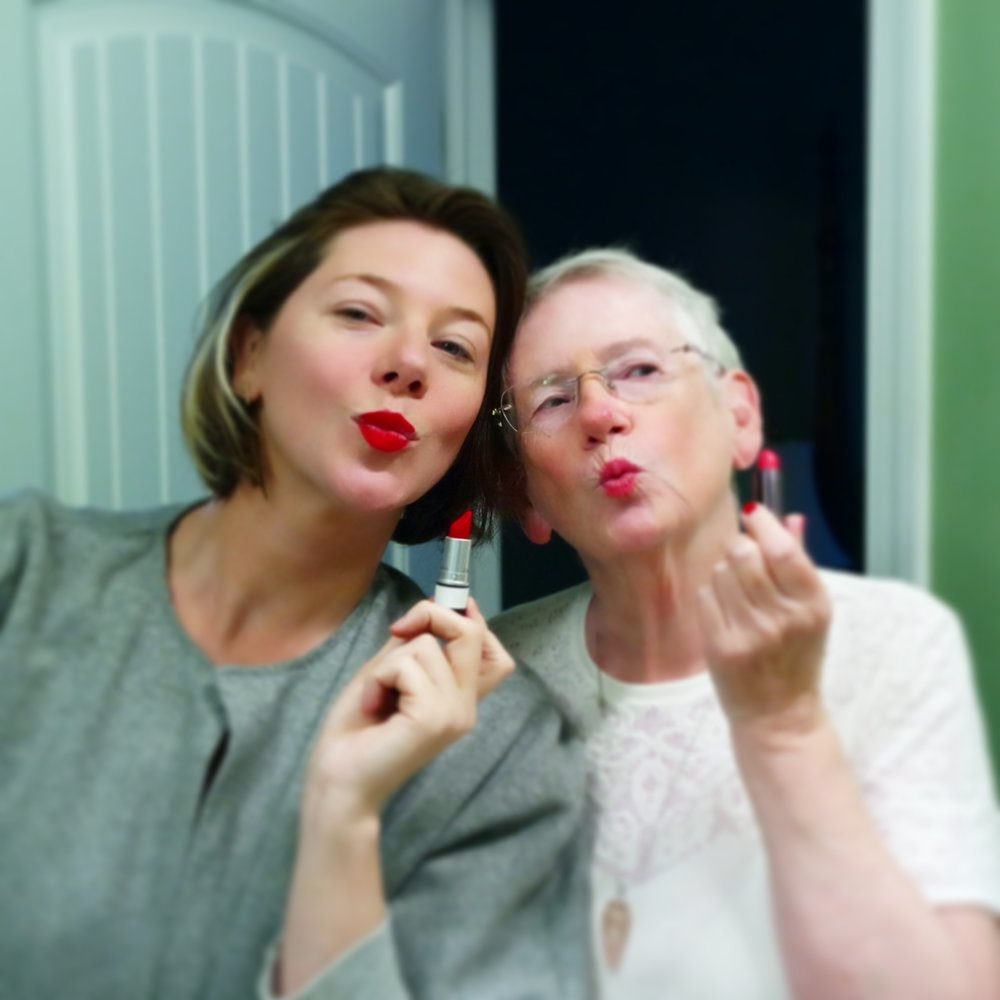 - Hello! I'm Kitty.  Here I am with one of my great muses (and Club Macaron member), my Mama, savoring one of life's simple joys, bright red lipstick.  My passion and purpose in life is simple: allow spirit to speak through the senses, and help others to feel the same. My journey has ranged from convent candidate to burlesque star.  I love all things glamorous, elegant and inviting.  I think the sexiest thing in the world is a person who speaks the truth and cares genuinely about other humans.  I enjoy exploring both the agony and the ecstasy of life; the deep, bitter espresso and the frothy cream on top. I have a deep devotion to beauty.  I created Club Macaron because sensuality, spirituality and style are the three things I could talk about for the rest of time and never get bored, and because it is the kind of club I'd be extremely proud to be a member of.   I come to you as both teacher and companion on the journey.  I not only lead the group, I practice right alongside you. The tools, experiences and coaching of Club Macaron are designed to lead you to your own unlimited inner resource of courage, while the community cheers you on loudly and throws confetti on your path.  It would be not only my pleasure but my honor to welcome you as a member.  Here's to the beginning of a fine romance!