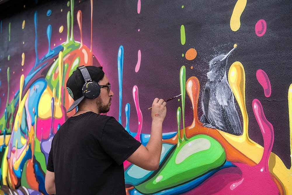 DASIC AT WORK ON HIS MURAL INSIDE THE WYNWOOD WALLS