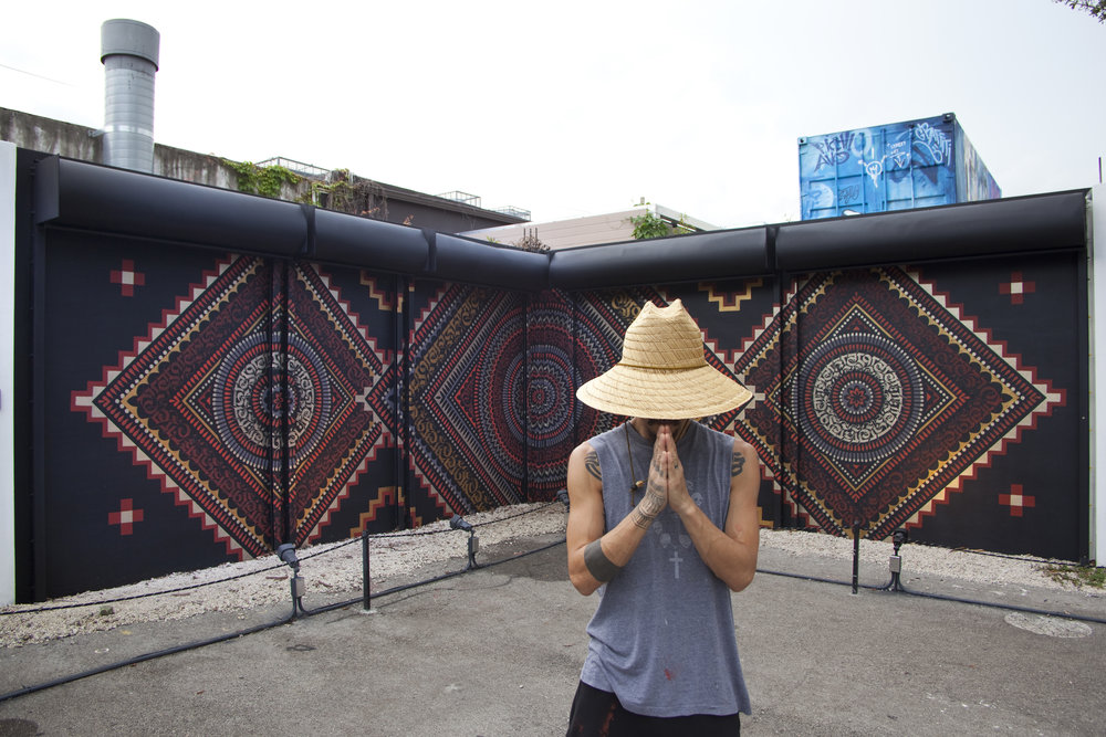 CRYPTIK IN FRONT OF HIS MURAL INSIDE THE WYNWOOD WALLS