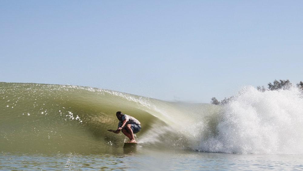 Futuristic wave, ancient surfboard: Taylor Jenson on a self-shaped alaia. Photo: Lippman