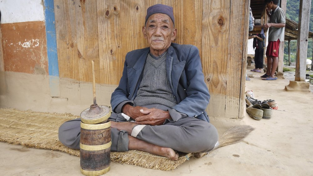 an old man enjoying his Tumba - a traditional beer-like drink served in the wooden tumblers.